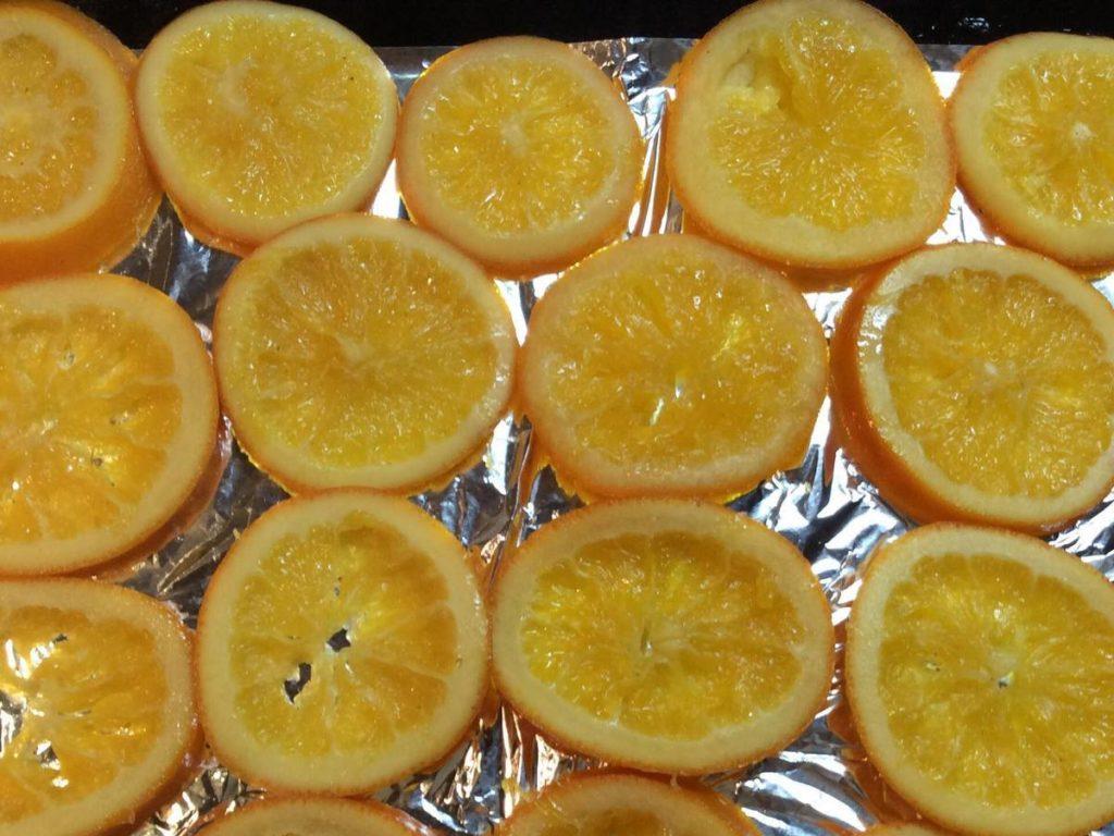 На застелене фольгою деко викладаємо кружальця апельсинів і ставимо в розігріту духовку