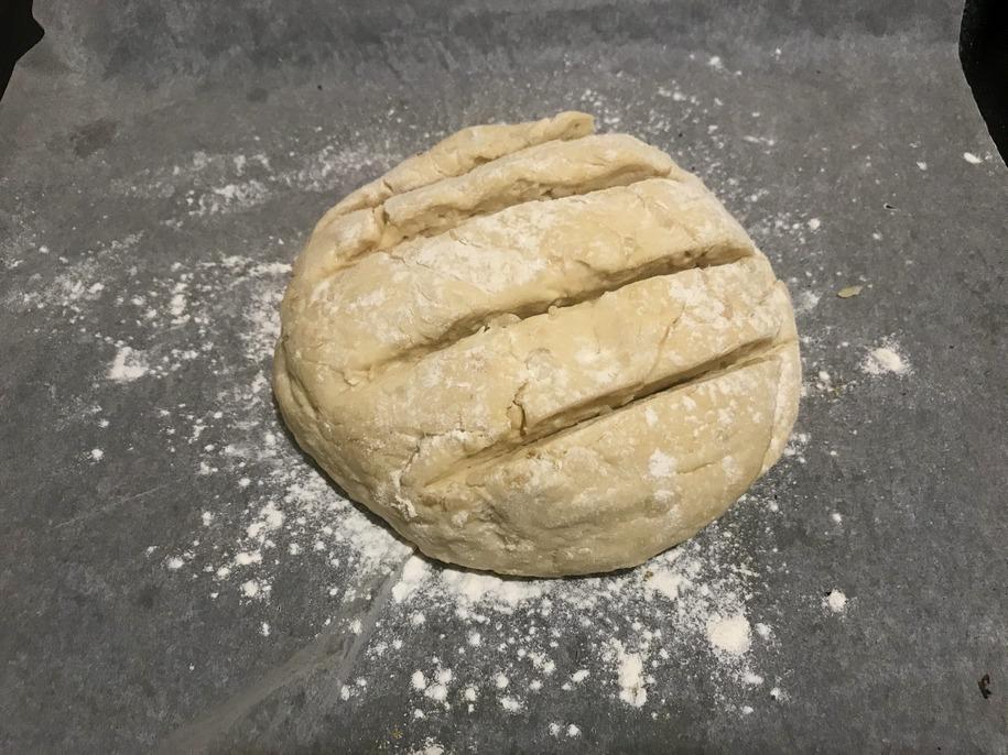 Кладемо хліб на деко, вистелене пергаментом, присипаємо зверху борошном, робимо надрізи (за бажання)